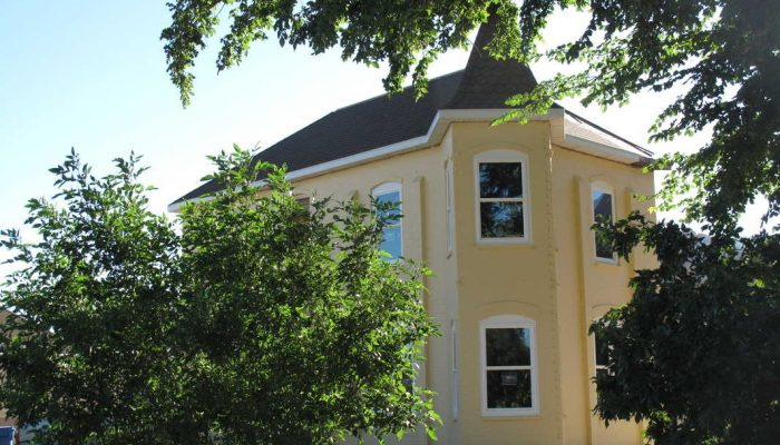 Old yellow two-story restored pioneer house in center of town